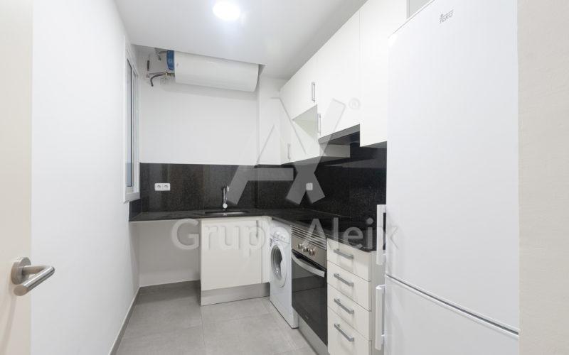 Cocina equipada con nevera combi, lavadora, horno y placas de vitrocerámica.